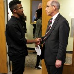Student activist John Gillespie (left) and Interim President Timothy Chandler (right) shake hands at the end of the night.