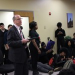 Interim President Timothy Chandler (left) standing before student protestors.