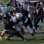 Towson players tackle a New Hampshire opponent. Photo by Joe Noyes.