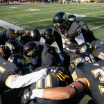 Football players huddle during the game. Photo by Joe Noyes.