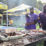 A group of alumni stand around the grill at the alumni tailgate.