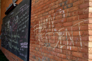 """Chalking in Freedom Square that reads """"#Not my president."""" In the background,messages of support on the blackboard. Photo by Cody Boteler."""