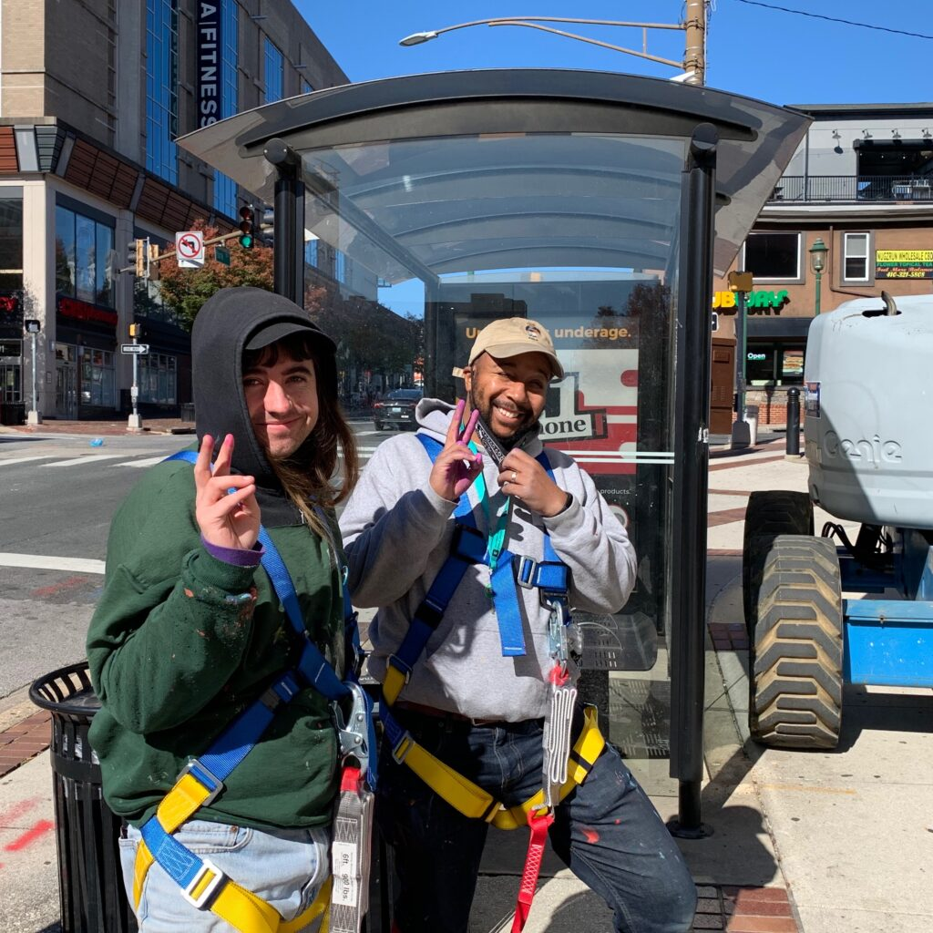 Artist Ryan Adams is pictured with artst Bee James, holding up peace signs as they stand on the sidewalk beside the Baltimore County Public Library where the mural is being painted. Still wearing harnesses from standing on boom lifts all day, they are smiling as their first day of painting is complete.