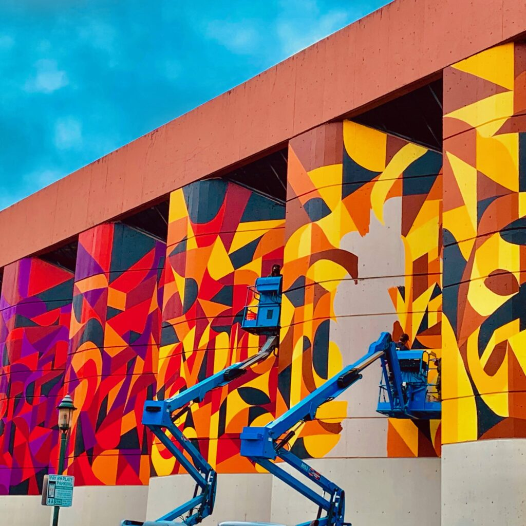 The face of the Baltimore County Library where the mural is being painted. Of the six panels of wall being painted, the first through fourth are complete. The artists are standing on two separate boom lifts painting the fifth wall panel. The sixth panel is complete. The mural has a gradient color scheme, more purple on the far left panel, progressing to red, to orange, to yellow on the far right panel.